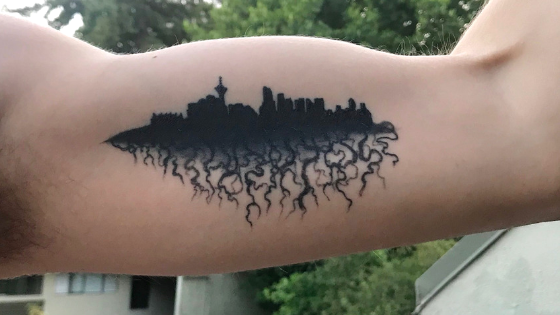 tattoo of the silhouette of vancouver with roots coming out of the bottom